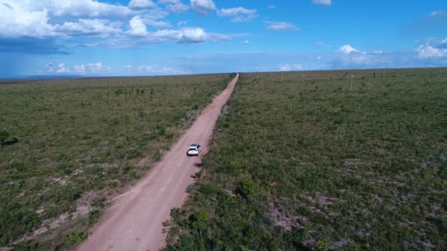 tracking shot of drone following car at landscape of road in cerrado in tocantins, brazil - tocantins stock videos and b-roll footage