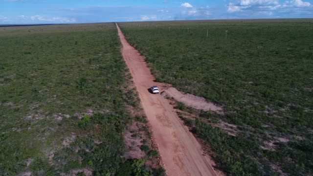 tracking shot of drone following car at landscape of road in cerrado in tocantins, brazil - latin america stock videos & royalty-free footage