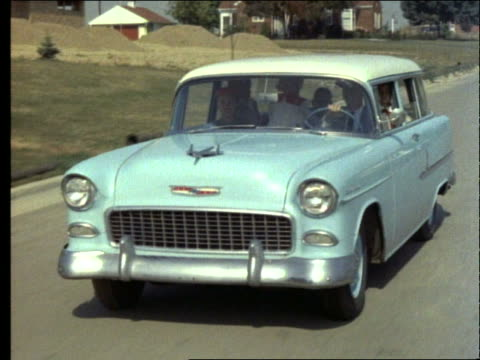 1955 tracking shot of family in blue station wagon on suburban street / chevrolet - chevrolet stock videos & royalty-free footage