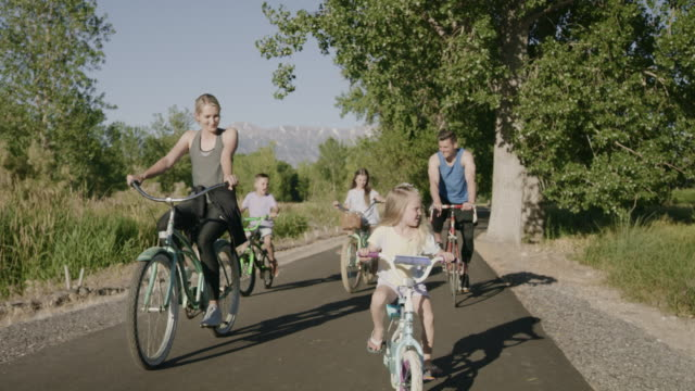 vídeos de stock, filmes e b-roll de tracking shot of family riding bicycle on path in park / saratoga springs, utah, united states - plano americano