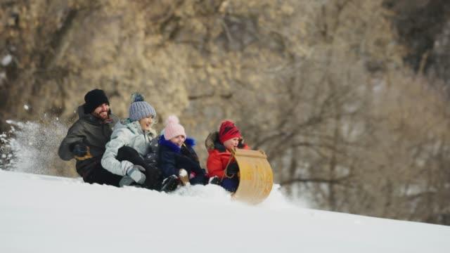 vídeos y material grabado en eventos de stock de tracking shot of family riding toboggan downhill in winter snow / south fork, utah, united states - tobogan