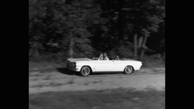 1962 tracking shot of family traveling by car on road - dog convertible stock videos & royalty-free footage