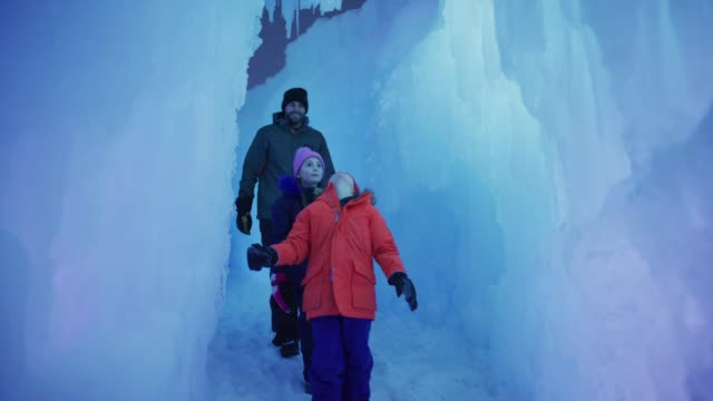 tracking shot of father and children walking in glowing ice castle tunnel / midway, utah, united states - exploration stock videos & royalty-free footage
