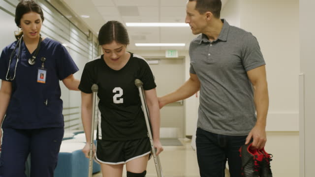 Tracking shot of father and smiling daughter walking with crutches talking to nurse in hospital / Salt Lake City, Utah, United States