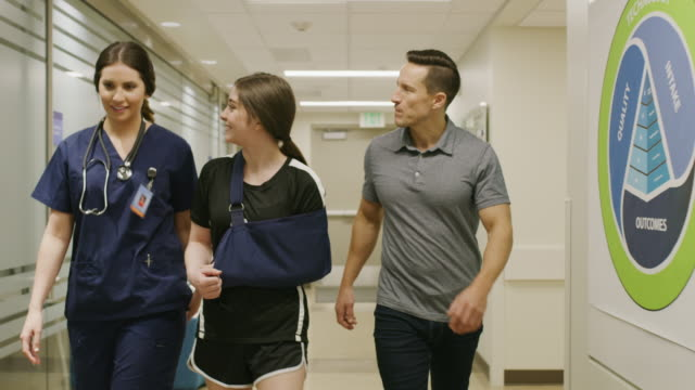 Tracking shot of father and smiling daughter with arm in sling talking to nurse in hospital / Salt Lake City, Utah, United States