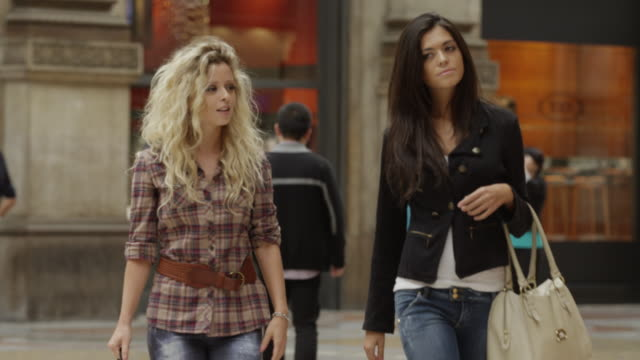 tracking shot of friends walking in shopping mall / milan, italy - consumerism stock videos and b-roll footage