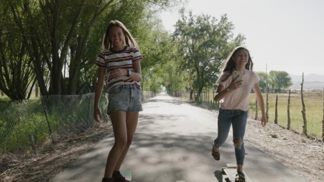 vídeos de stock e filmes b-roll de tracking shot of girl on skateboard photographing friend then posing for cell phone selfie / saratoga springs, utah, united states - perto
