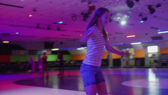 stockvideo's en b-roll-footage met tracking shot of girl skating awkwardly at roller skating rink / orem, utah, united states - driekwartlengte
