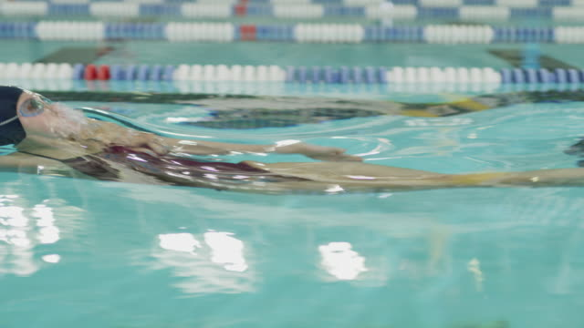 tracking shot of girl swimming backstroke in swimming pool / provo, utah, united states - backstroke stock videos & royalty-free footage