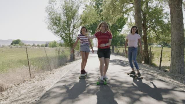vídeos de stock e filmes b-roll de tracking shot of girls riding skateboards on park path posing for cell phone selfies / saratoga springs, utah, united states - perto