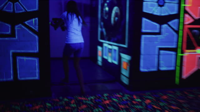 tracking shot of girls running and shooting while playing laser tag / orem, utah, united states - glowing doorway stock videos & royalty-free footage