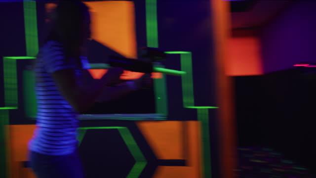 stockvideo's en b-roll-footage met tracking shot of girls running and shooting while playing laser tag / orem, utah, united states - laser