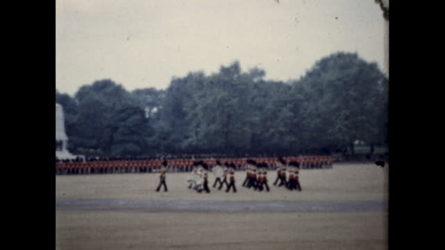 tracking shot of group of british royal guards marching across big square - drill stock videos & royalty-free footage