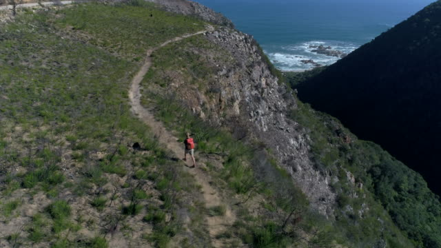 Tracking shot of hiker female on mountain trail