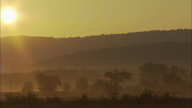 Tracking shot of horizon sunset silhouetted valleys warm and golden