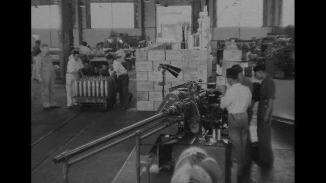 tracking shot of indonesian men at workstations / pan busy factory floor to men pushing heavy cart loaded with vertical ammunition shells intent face... - artiglieria video stock e b–roll