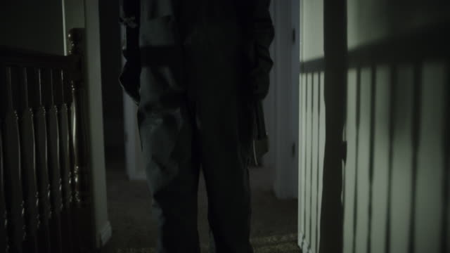 vidéos et rushes de tracking shot of intruder holding axe walking in home corridor at night / springville, utah, united states - springville utah