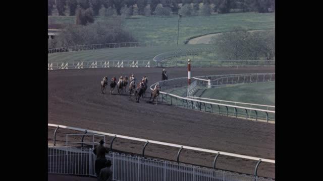 tracking shot of jockeys riding horses on sports track during race, santa anita park, arcadia, california, usa - 競走馬点の映像素材/bロール