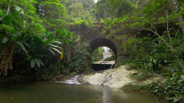 vídeos de stock e filmes b-roll de tracking shot of jungle stream, waterfall seen through stone arch - 2013