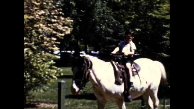 tracking shot of little boy in white shirt and shorts riding a white horse along dirt road; short fence and trees in the background - one boy only stock videos & royalty-free footage