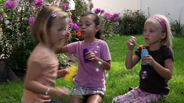 Tracking shot of little girls blowing bubbles in a flowery garden.