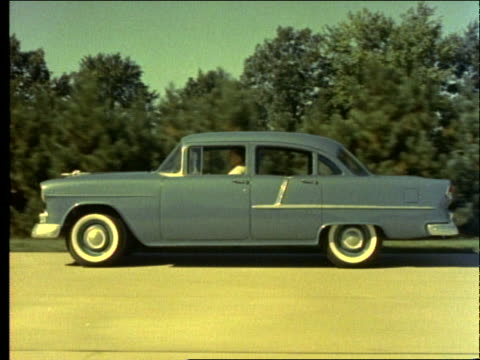 stockvideo's en b-roll-footage met 1955 tracking shot of man driving blue car on country road / chevrolet - 1955