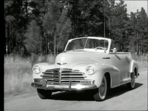 b/w 1948 tracking shot of man driving chevrolet fleetmaster convertible on country road - chevrolet stock videos & royalty-free footage