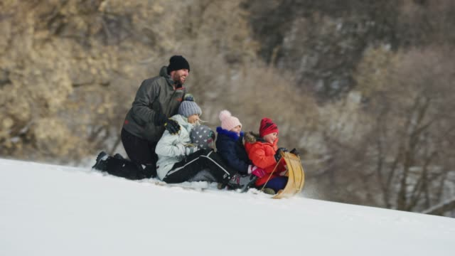tracking shot of man pushing family on toboggan downhill in winter snow / south fork, utah, united states - utah stock videos & royalty-free footage