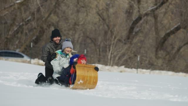 tracking shot of man pushing family on toboggan downhill in winter snow then falling / south fork, utah, united states - pushing stock videos & royalty-free footage