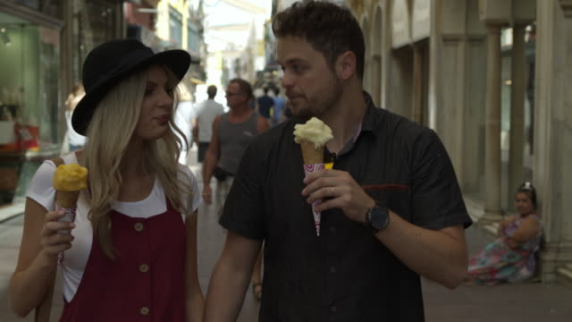 Tracking shot of man smearing ice cream cone on nose of woman in city street / Seville, Sevilla, Spain