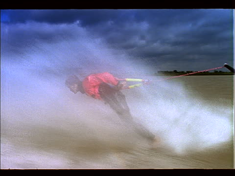 vídeos y material grabado en eventos de stock de tracking shot of man waterskiing barefoot + doing stunt - waterskiing