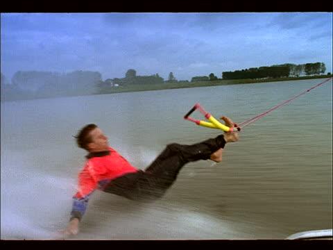 vídeos y material grabado en eventos de stock de tracking shot of man waterskiing barefoot + doing stunts - waterskiing