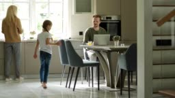 Tracking shot of man working on laptop sitting at table in domestic kitchen. Little daughter running downstairs to him, caring mother giving her glass of orange juice. Family gathering at table