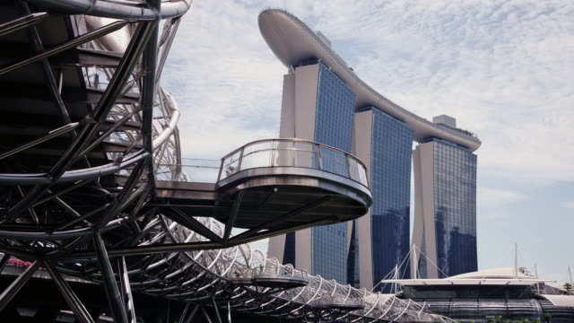 ws tl tracking shot of marina bay sands hotel and casino and helix bridge - helix bridge stock videos & royalty-free footage