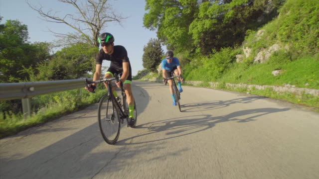 stockvideo's en b-roll-footage met tracking shot of men race cycling on bicycles, riding on road bikes in italy. - slow motion - mid volwassen mannen