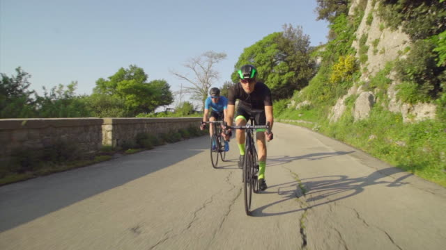 tracking shot of men race cycling on bicycles, riding on road bikes in italy. - slow motion - 30 39 years stock videos & royalty-free footage