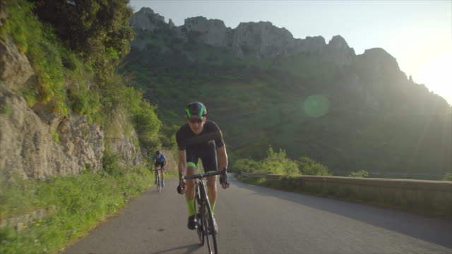 tracking shot of men race cycling on bicycles, riding on road bikes in italy. - slow motion - tracking shot stock videos & royalty-free footage