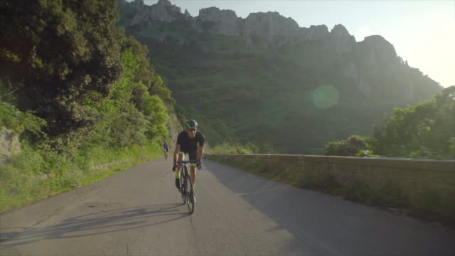 tracking shot of men race cycling on bicycles, riding on road bikes in italy. - slow motion - プロトン点の映像素材/bロール