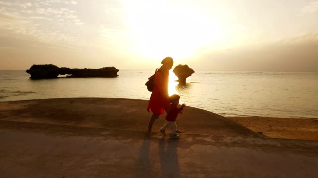 Tracking shot of mother and daughter walking on the beach.