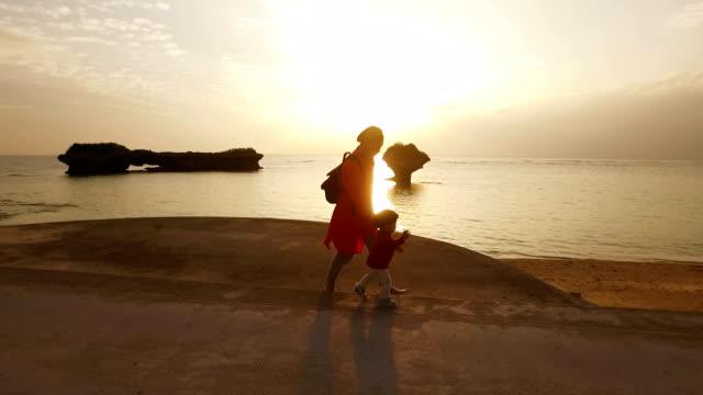 Tracking shot van moeder en dochter lopen op het strand.