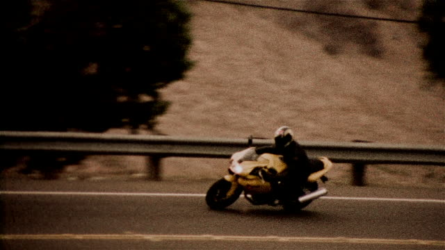 tracking shot of motorcyclist rounding bend / passing camera - biker jacket stock videos and b-roll footage