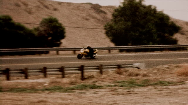 tracking shot of motorcyclist traveling on highway - biker jacket stock videos and b-roll footage