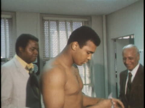 tracking shot of muhammad ali dressed in a suit as he walks into an office. he is surrounded by reporters. cut to press photographers lining up their... - アリ点の映像素材/bロール