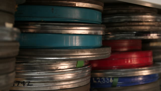 Tracking shot of multicoloured film cans sitting on a shelving unit