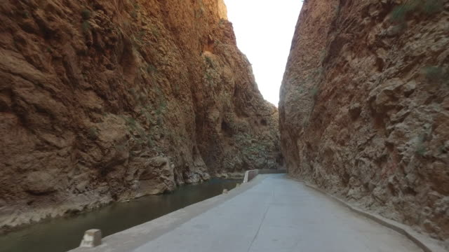 tracking shot of narrow road amidst rocky mountains - ravine stock videos & royalty-free footage