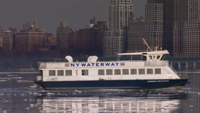 stockvideo's en b-roll-footage met tracking shot of new york waterway ferry moving along an ice filled hudson river in front of the upper west side skyline. - ferry