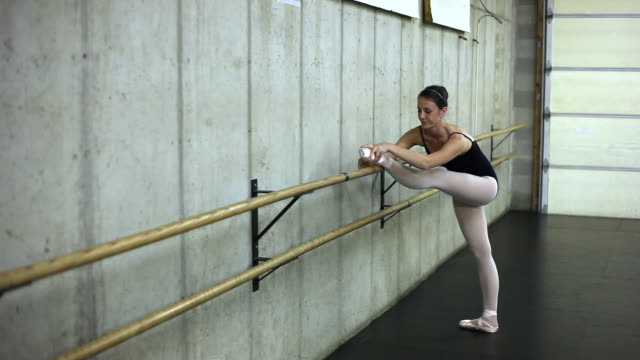 tracking shot of of a ballet dancer stretching her leg on the barre. - barre stock videos & royalty-free footage