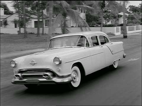 b/w 1954 tracking shot of oldsmobile 88 driving past houses + palm trees on suburban street / florida? - general motors stock videos & royalty-free footage