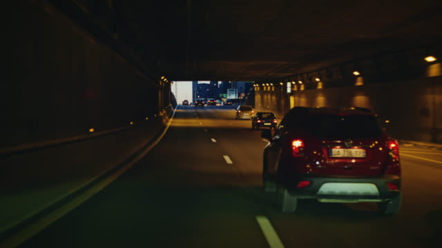 Tracking shot of Paris expressway looking at the Défense district buildings, at dusk