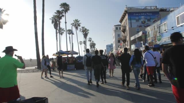 tracking shot of pedestrians walking at venice beach on ocean avenue, sant monica, los angeles, la, california, usa, north america - ocean avenue stock videos & royalty-free footage
